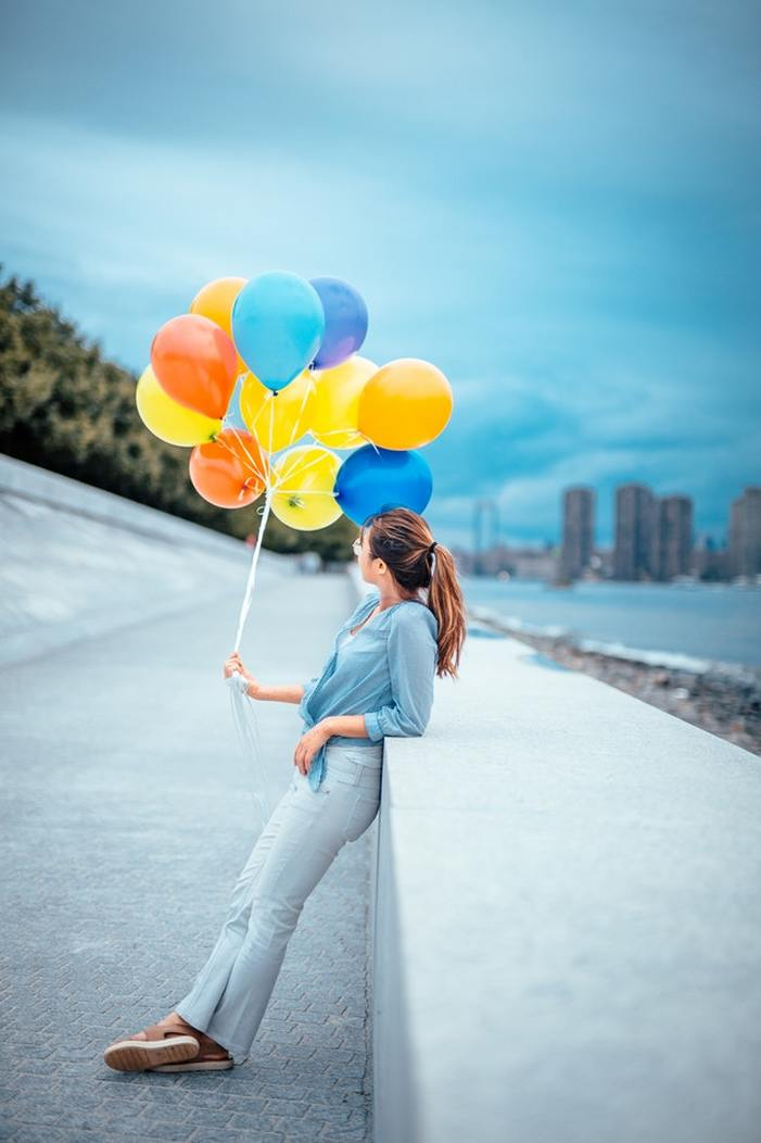 woman_with_balloons_feeling_happy_about_lyric_hearing_aids