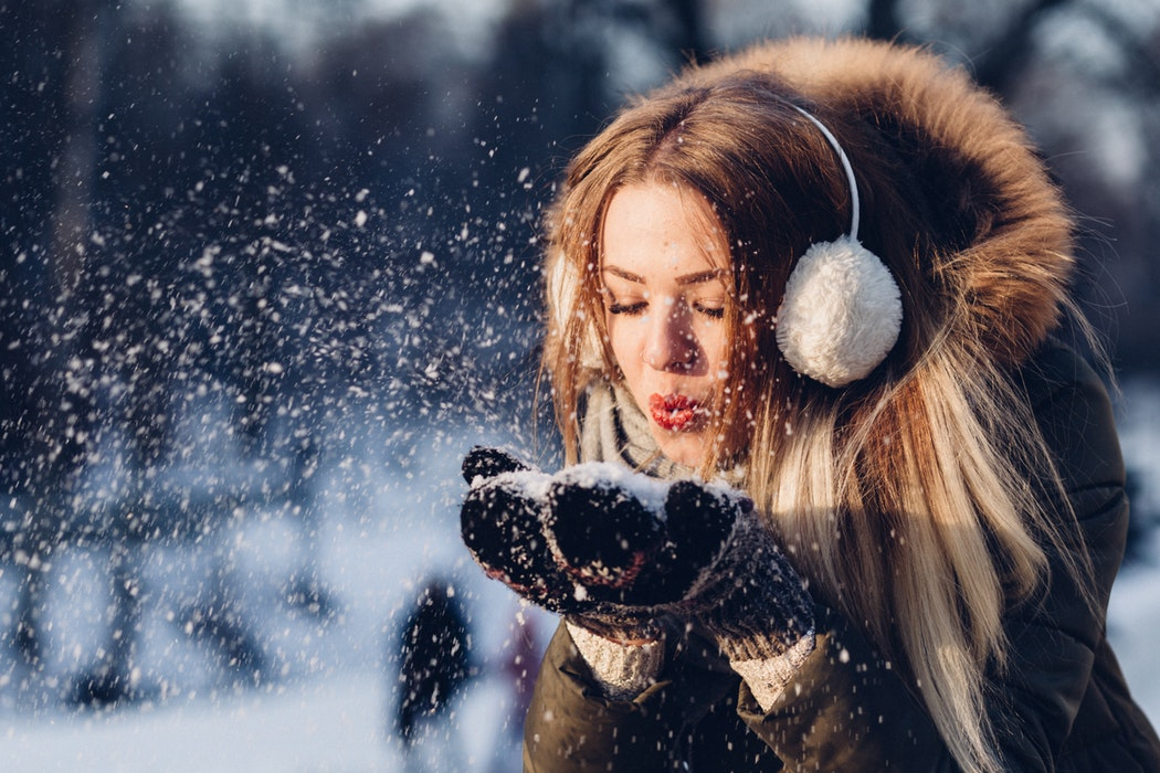 woman_enjoying_winter_and_covering_her_hearing_aids_with_earmuffs